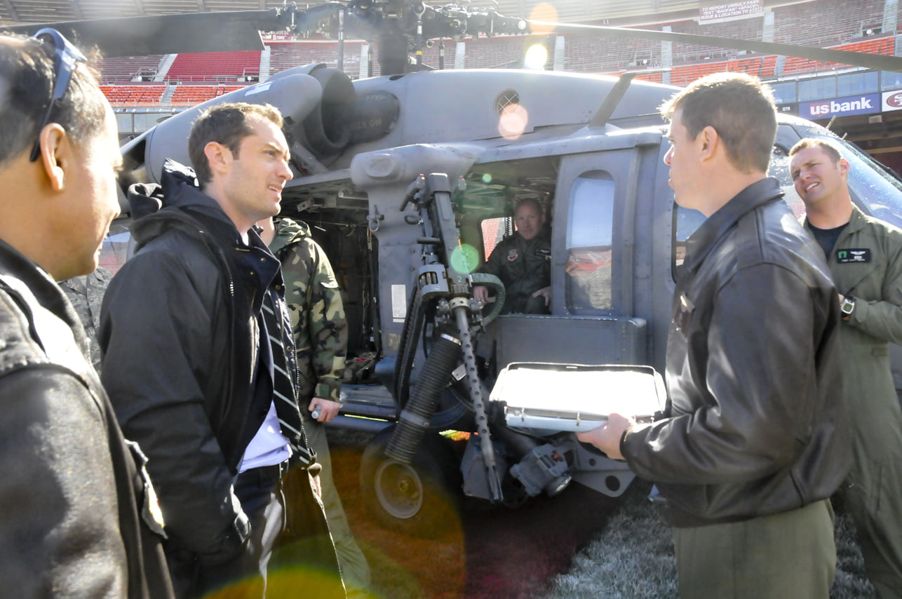 """Actor Jude Law, greets members from the 129th Rescue Squadron during the making of a movie called """"Contagion"""" at Candlestick Park Stadium, San Francisco, Calif., Feb 16, 2011. The 129th Rescue Squadron from Moffett Federal Airfield, California Air National Guard assisted in a shooting sequence by providing an HH-60G Pave Hawk helicopter. (Air National Guard photo by Tech. Sgt. Ray Aquino/RELEASED)"""